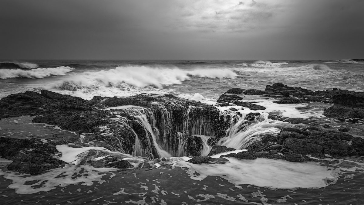 Continuous ocean waves pouring into Thor's Well along the coast.