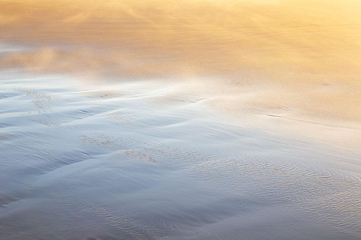 A wet, sandy shoreline lit up by sunset.