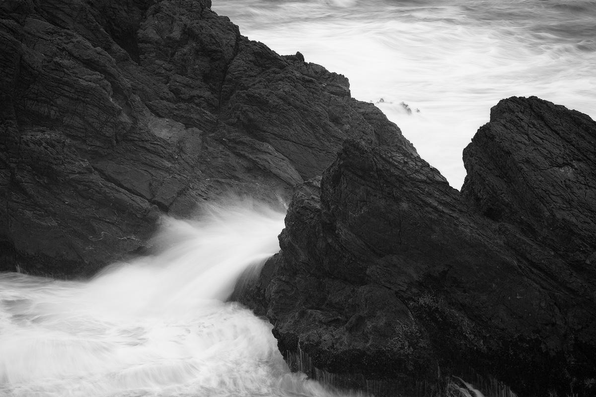 Ocean water flowing smoothly between sea stacks along the Oregon Coast.