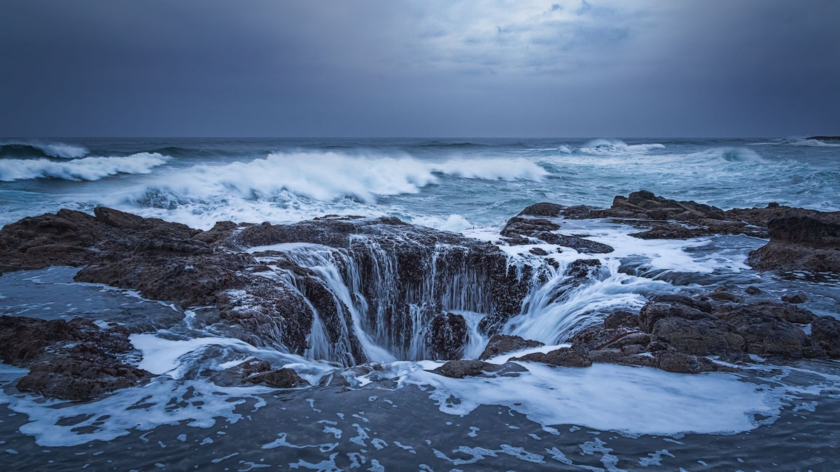 Ocean waves pouring into Thor's Well. I loved how the sun was filtered through clouds and casted a spot light right onto the...